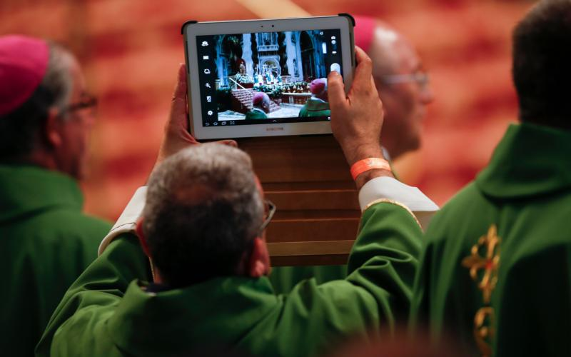 """A priest take pictures with a tablet as Pope Francis celebrates Mass in St. Peter's Basilica at the Vatican in this July 7, 2013, file photo. The pope, at his Nov. 8 general audience, said it's """"an awful thing"""" for people to take cellphone photos at Mass. (CNS photo by Tony Gentile/Reuters)"""