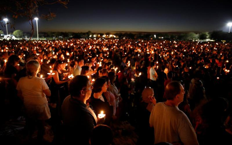 People attend a candlelight prayer vigil Feb. 15 for the victims of a mass shooting at nearby Marjory Stoneman Douglas High School in Parkland, Fla. At least 17 people were killed in the Feb. 14 shooting. The suspect, 19-year-old former student Nikolas Cruz, is in custody. (CNS photo by Carlos Garcia Rawlins/Reuters)
