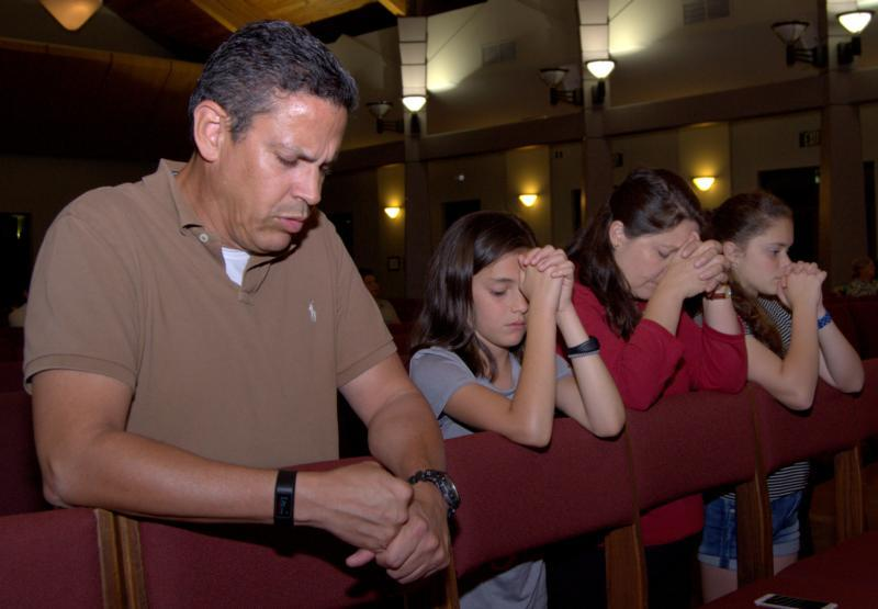 Marcos and Luz Gonzalez pray alongside their daughters, Sabrina and Laura, far right, Feb. 15 at Mary Help of Christians Catholic Church in Parkland, Fla. The family and others were attending a prayer service for victims of the mass shooting Feb. 14 at nearby Marjory Stoneman Douglas High School. (CNS photo by Jim Davis/Florida Catholic)