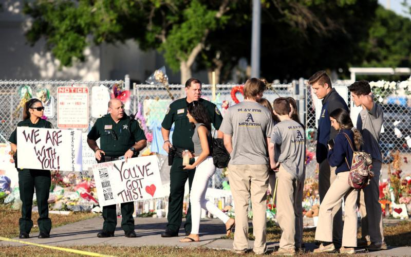 "Police and law enforcement officers show their support as students arrive Feb. 28 at Marjory Stoneman Douglas High School in Parkland, Fla., for the first time since the Feb. 14 mass shooting. The chairmen of the U.S. bishops' committees on domestic policy and Catholic education issued a joint statement March 5 calling on the nation's leaders to come up with ""common-sense gun measures."" (CNS photo by Mary Beth Koeth, Reuters)"