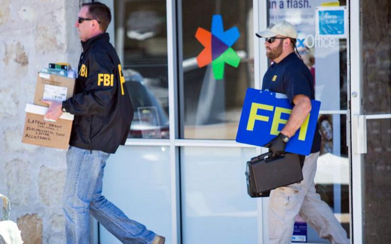 """FBI agents are seen carrying items out in paper bags and boxes March 20 from a FedEx store in Austin, Texas, after a fifth bombing. """"These appalling attacks have killed and injured innocent people, young adults, and children who were in their homes, bicycling on the street, and working at their jobs,"""" Archbishop Gustavo Garcia-Siller of San Antonio and Bishop Joe S. Vasquez of Austin said in a March 20 statement. (CNS photo by Thao Nguyen/EPA)"""