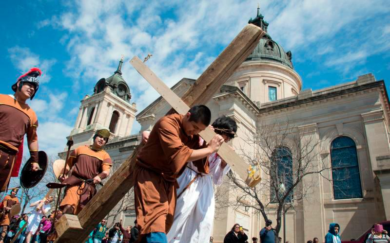 Youth depicting Simon of Cyrene and Jesus carry a cross past the Cathedral of the Immaculate Conception March 25 in Wichita, Kan. Police closed the streets around the cathedral for the youth group's Stations of the Cross. About 200 parishioners participated in the event. (CNS photo by Christopher Riggs/Catholic Advance)