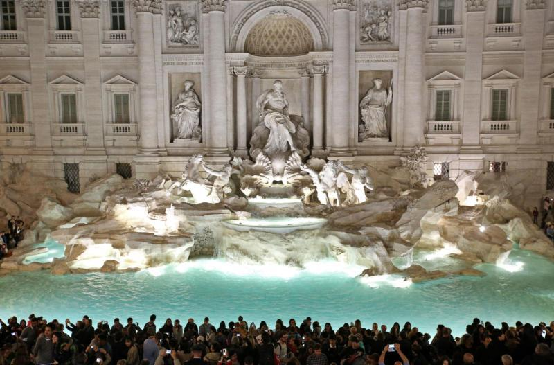 People gather in front of the landmark Trevi Fountain after its 2015 restoration in Rome. While millions of tourists throw a coin over their shoulder into the fountain hoping to return to Rome one day, the money scooped out of the fountain each week offers more concrete hope to the city's poor. (CNS photo by Alessandro Di Meo/EPA)