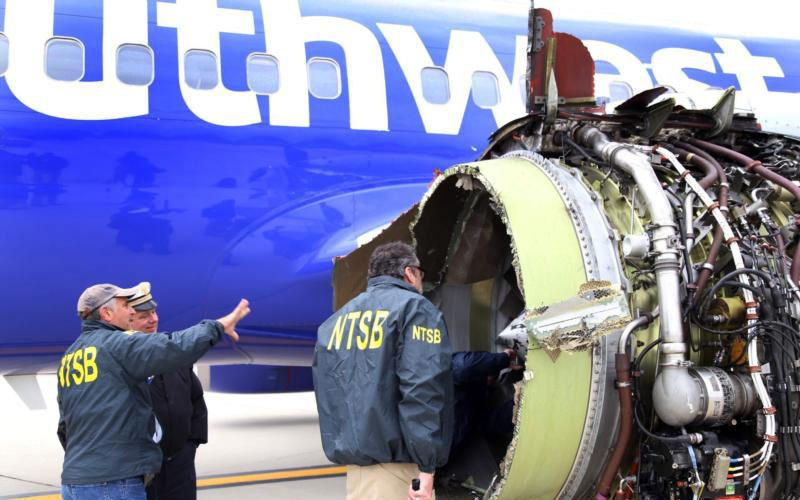 Investigators with the National Transportation Safety Board examine damage to the engine of a Southwest Airlines plane in Philadelphia April 17. Flight 1380 took off that morning from LaGuardia in New York, bound for Dallas, when the engine broke apart in midair and burst through a window, sucking passenger Jennifer Riordan partially out. She later died from her injuries. (CNS photo by NTSB handout via Reuters)