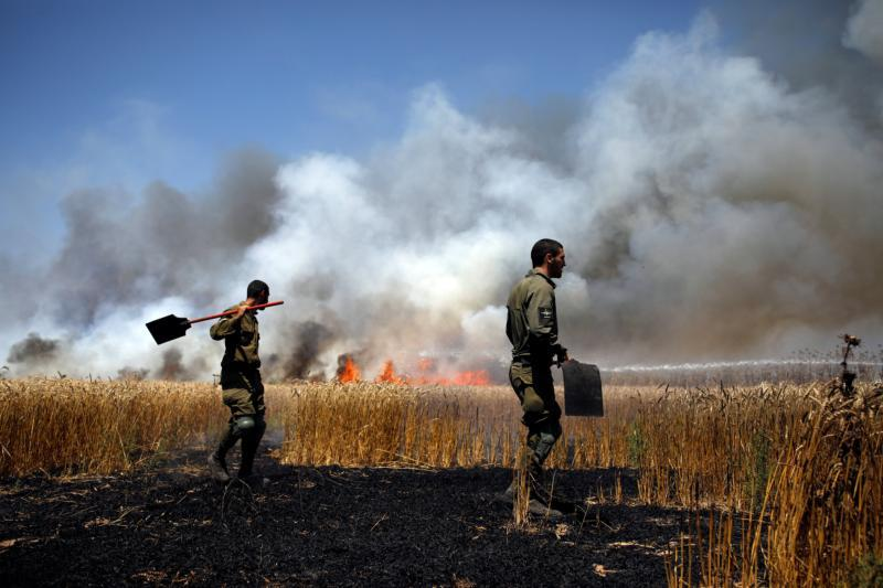 Israeli soldiers near near Mefalsim extinguish a fire on the Israeli side of the border between Israel and Gaza May 14. (CNS photo by Amir Cohen/Reuters)