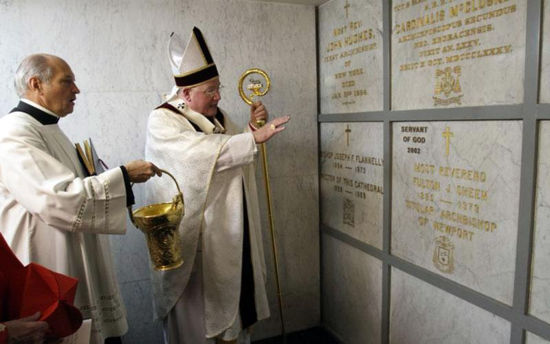 Then-Archbishop Timothy M. Dolan of New York blesses the tomb of Archbishop Fulton J. Sheen in the crypt of St. Patrick's Cathedral in New York City on Dec. 9, 2009, the 30th anniversary of the prelate's death. On June 8, the New York Superior Court ruled in favor of Joan Sheen Cunningham, a niece of Archbishop Sheen, saying his remains should be returned to the Diocese of Peoria, Ill., his home diocese. (CNS photo by Gregory A. Shemitz)