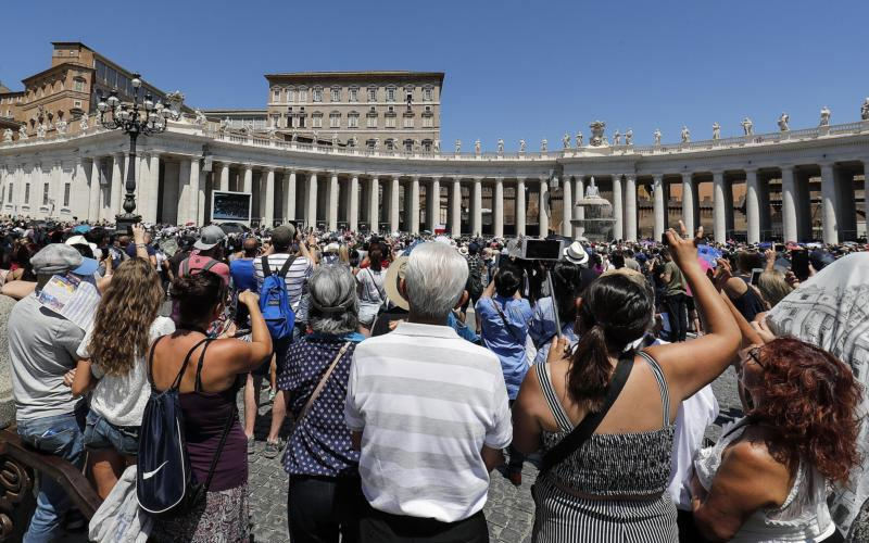 Pilgrims take pictures as Pope Francis leads the Angelus from the window of his studio overlooking St. Peter's Square July 8 at the Vatican. (CNS photo by Riccardo Antimani/EPA)