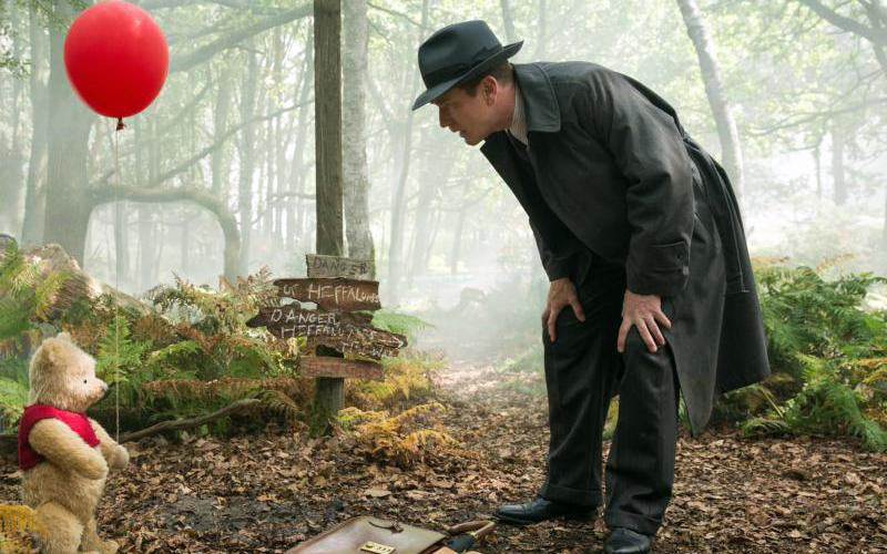 "Ewan McGregor, as Christopher Robin, shares a scene with Winnie the Pooh in the live-action adventure movie ""Christopher Robin."" (CNS photo by Laurie Sparham, Disney)"