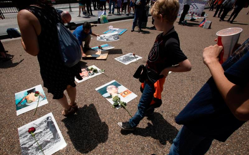 People in Washington look at photos from World War II near the White House Aug. 9. The photos were part of a Catholic prayer service of repentance for the use of nuclear bombs on Japan in 1945. (CNS photo by Tyler Orsburn)