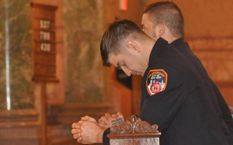 Firefighters pray during a Sept. 11 Mass at St. Joseph's Co-Cathedral in Brooklyn, N.Y., on the 17th anniversary of the the 9/11 terrorist attacks. Nearly 3,000 people died in the 2001 attacks in New York City and Shanksville, Pa., and at the Pentagon. (CNS photo by Ed Wilkinson/The Tablet)