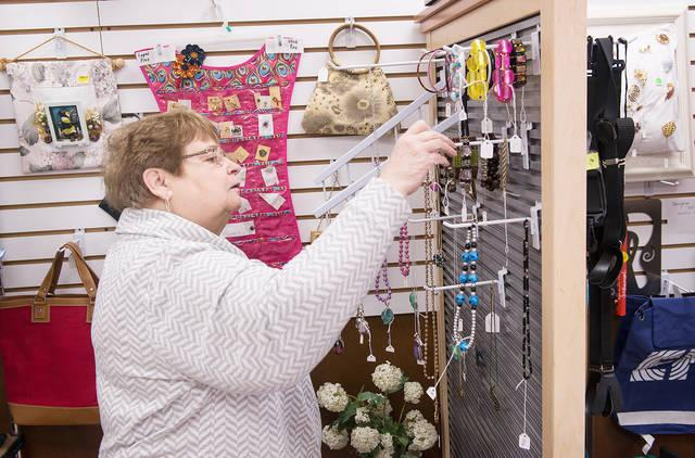 <p>Patti Frawley hangs items for sale at Life Solutions of Hamlin Jan. 10.  (Courier photo by John Haeger) </p>