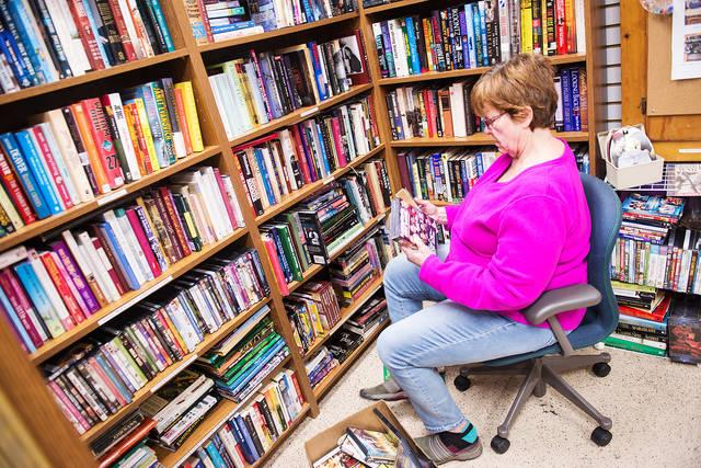 <p>Donna Butterbaugh sorts DVDs and books at Life Solutions of Hamlin Jan. 10.  (Courier photo by John Haeger) </p>