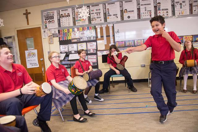 <p>St. Francis-St. Stephen School fifth-grader Evan Espinosa (center) leads classmates in a drum circle at the Geneva school Jan. 24. (Courier photo by John Haeger) </p>