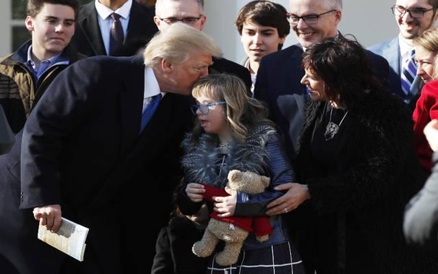 <p>President Donald Trump greets a girl after addressing attendees of the annual March for Life rally from the Rose Garden of the White House in Washington Jan. 19. The live feed was projected onto a large video screen during the rally on the National Mall.  </p>