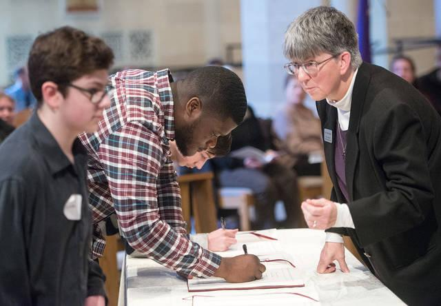 <p>Catechumens sign their names in the Book of Elect during the Feb. 18 Rite of Election and Call to Continuing Conversion at Sacred Heart Cathedral in Rochester.  </p>