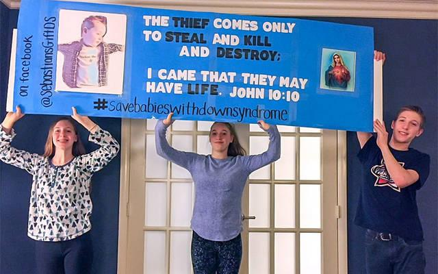 <p>Sebastian Black's older siblings, Genevieve (from left), Camille and Thad, hold up the sign they carried during January's March for Life rally in Washington, D.C.  </p>