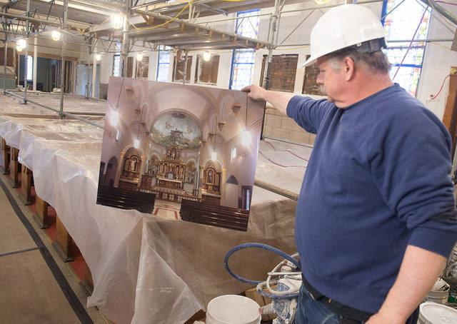 <p>Project manager Frank Marianacci holds up an artist's rendering April 11 of some of the renovation work being done at Our Lady of Victory Church in Rochester. It is the first major renovation to be undertaken at the church since a fire there in 1912. (Courier photo by John Haeger) </p>