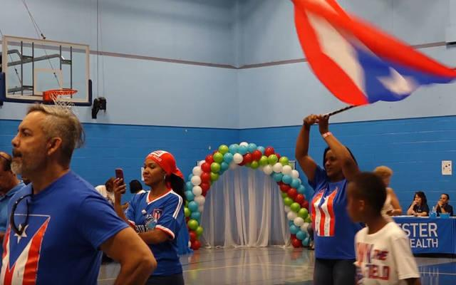 <p>Irene Sanchez waves the Puerto Rican flag during the Puertorriquenos Unidos en la Distancia Summer Kickoff Event at the David F. Gantt Recreation Center July 14. (Courier photo by Gina Capellazzi) </p>
