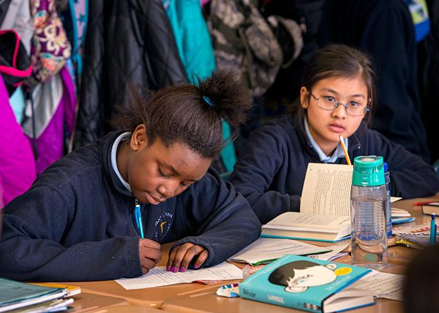 Sixth-graders Marguerite Kesinge (left) and Jahka Ley participate in a class exercise at Rochester's Holy Cross School Jan 24. The school participates in a program that helps refugee children attend Catholic schools.