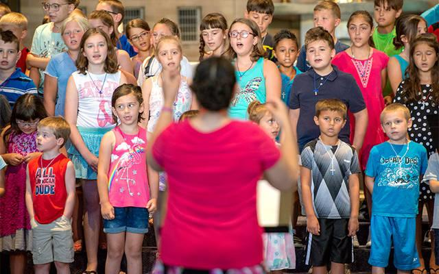 <p>A volunteer music teacher leads a song during summer camp at St. Charles Borromeo, Greece, July 20. Volunteers working with children must undergo screening and safe-environment training, and abide by a code of conduct. (Courier photo by Jeff Witherow) </p>