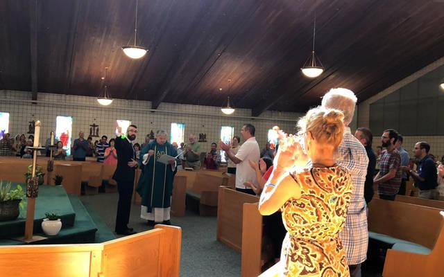 <p>Jimmy Muscatella receives a blessing from Father Michael Schramel, pastor of Parish of the Holy Family in Gates. (Photo by Natalie Costanza)  </p>