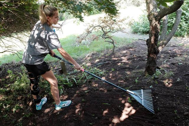 <p>Ellie Johnson of St. Benedict Parish in Canandaigua and East Bloomfield rakes a garden area at a home in Victor Aug. 2 as part of the parish's annual Summer Service Camp.  </p>