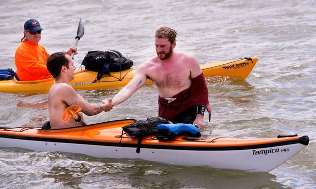 <p>Richard Henahan shakes hands with one of the kayakers who accompanied him Aug. 5 as he swam the length of Canandaigua Lake to raise funds for Mary's Place Refugee Outreach in Rochester.  </p>