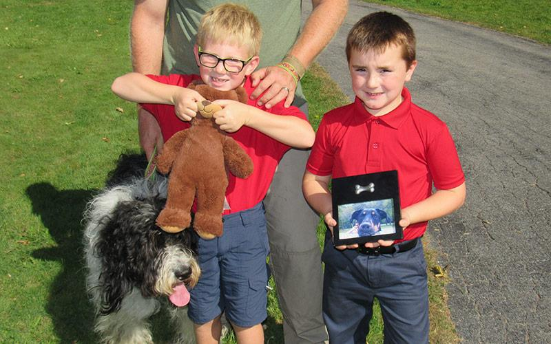 Gideon Mann with his dog and a stuffed animal friend and Johnathan Kellen with his pet's picture.