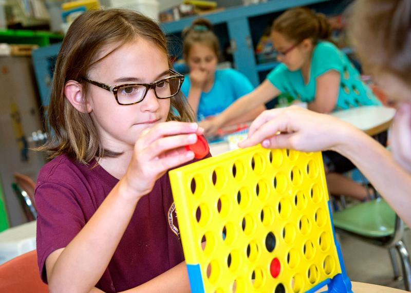 Nine-year-old Isabella Guido (left) plays Connect Four with Riley Kettles (right) during an after school program at Irondequoit's St. Kateri School June 15.