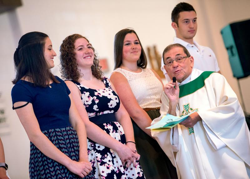 Tyler Dellina (back) and sisters Brittany (from left), Rachel and Nicole Ellison are recognized by Father Stephen Kraus during a June 11 Mass at St. Theodore Church in Gates that honored 2017 high-school graduates. The Ellison triplets say they are prepared to continue their faith lives at college.
