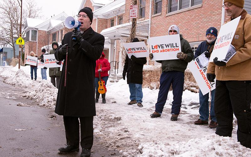 """Father William """"Mickey"""" McGrath prays the rosary during a Dec. 16 Stand Out for Life rally against abortion."""