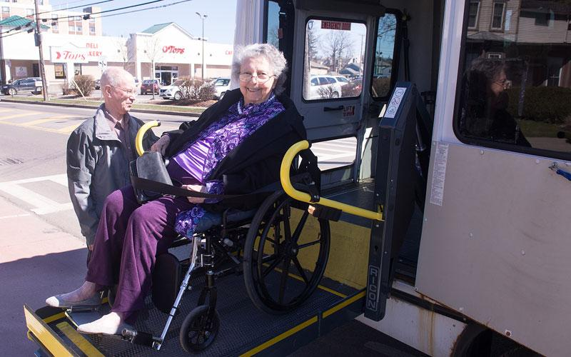 <p>Fred Proietti helps Helen Stewart onto the Sunday Bus following Mass at St. Michael Church in Penn Yan April 22. (Courier photo by John Haeger) </p>