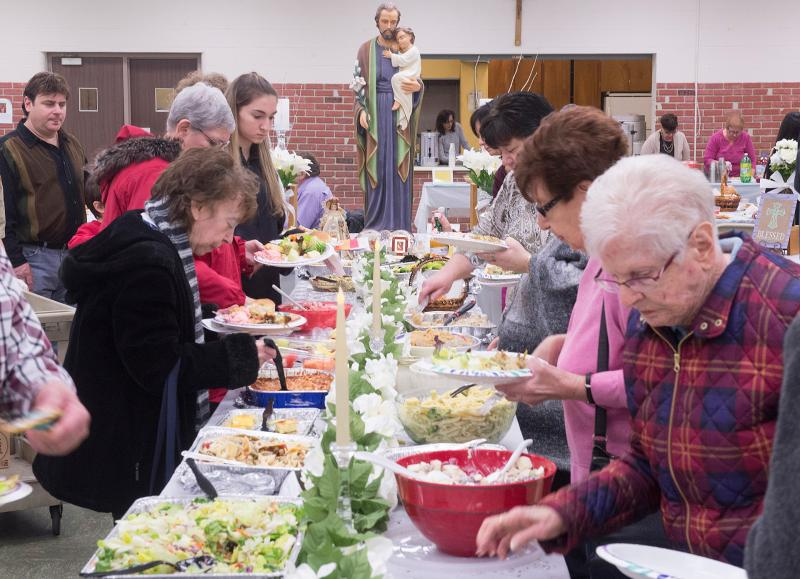 People make their way through the food at the St. Joseph's Table at Our Mother of Sorrows Church in Greece March 10.