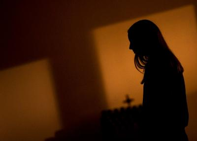 Youth-group member Kristin Phillips waits in the back of a darkened St. Matthew Church in Livonia during a Good Friday Tenebrae service April 14.