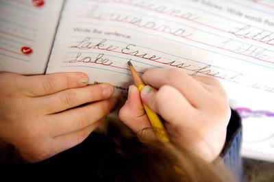 Third-grader Elliana Galusha works on her cursive Dec. 15 during a lesson in Jennifer Sheehan's class at St. Lawrence School in Greece.