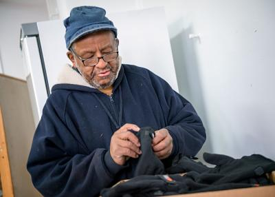 Vincent Haynes picks out gloves that were given away at Rochester's St. Peter's Kitchen Nov. 22.