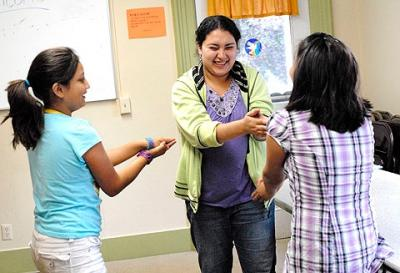 Cornell University student Roxana Orellana (center) plays an icebreaker game with 10-year-old Daniela Santacruz (left) and 11-year-old Alex Ventura July 28 at the Our Lady of Guadalupe Mission at St. Gregory Church in Marion.