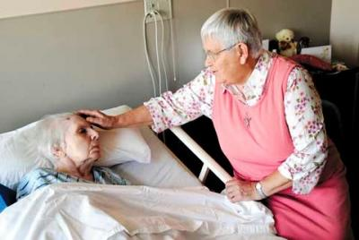 Sister Maria Kellner sits at the bedside of Sister Eleanor Seidewand Aug. 30 at the Sisters of St. Joseph Motherhouse in Pittsford. Sister Seidewand passed away Sept. 3.