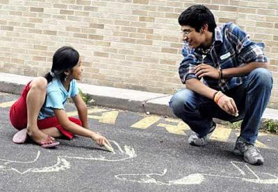 """Twenty teens learned about different faiths and took part in community-service projects as part of a Nazareth College program called """"The Next Generation: Living Together in a Multi-Religious Society."""" Above, participant Taaha Rehmani, 17, and 8-year-old Snow White draw with sidewalk chalk July 22 in the driveway of Mary's Place, a refugee ministry in Rochester."""