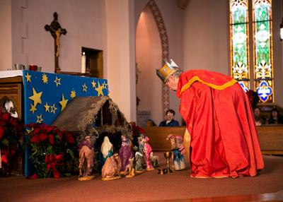 Kent Salisbury places a gift in front of the crèche at Penn Yan's St. Michael Church during a feast of the Epiphany celebration Jan 8.