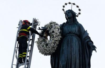 A firefighter places a wreath at the foot of a tall statue of Mary overlooking the Spanish Steps in Rome Dec. 8, the feast of the Immaculate Conception. Rome's firefighters have observed the tradition every year since 1857.