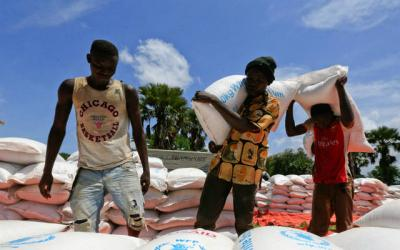 <p>Refugees from South Sudan unload food items from trucks Oct. 8 at a camp in Moyo, Uganda.  </p>