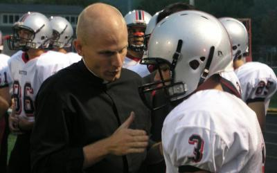 After a play during a 2009 football game, Father John Hollowell coaches Eddie Cmehil, a sophomore wide receiver and defensive back for Cardinal Ritter Junior/Senior High School's varsity football team in Indianapolis. (CNS photo by John Shaughnessy/The Criterion)