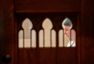 Carrie Guererro sits inside a confessional at Brockport's Nativity of the Blessed Virgin Mary Church during last year's Day of Penance, March 25, 2014.