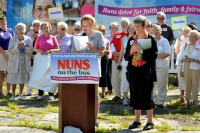 """Sister Simone Campbell (right), executive director of the Catholic social-justice lobby group NETWORK, listens to a speaker June 19 during a stopby the """"Nuns on the Bus"""" tour in Dubuque, Iowa."""