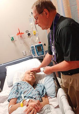 Father Willian endres offers anointing of the sick to a patient at Strong Memorial Hospital in 2005.