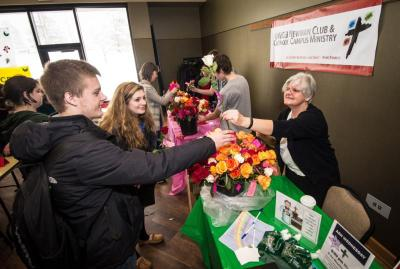 "Franciscan Sister Laura Zelten hands a rose to a university of Wisconsin-Green Bay student during the university's ""OrgSmorg"" event in the student center Feb. 3. The rose giveaway was part of True Love Week, organized by Catholic campus ministry groups to spread a message about abstinence."