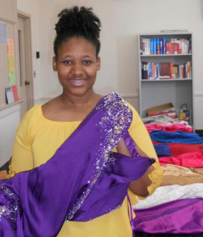 Ashley Wilson, a senior at Villa Angela-St. Joseph High School in Cleveland, displays some of the prom gowns May 18 that she collected for girls who were unable to afford one