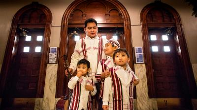A man stands with his three sons at St. Pius V Parish in St. Louis in this 2014 photo.