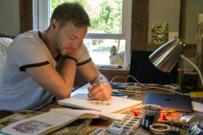 """Catholic cartoonist Ben Hatke sketches his character """"Zita the Spacegirl"""" in a studio in his Front Royal, Va., home May 17. His graphic novel series features a character who was named in honor of St. Zita"""